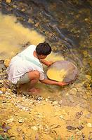 Hombre Yanomami buscando oro con zurco a orillas de un río, Amazonas, Venezuela.