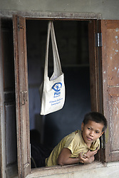 An unnamed boy looks from his school class window during mis morning break, with a Plan International school bag hanging up to keep clean.<br /> Viengpathana primary School,   Pha Oudom District, Bokeo Province, Lao PDR