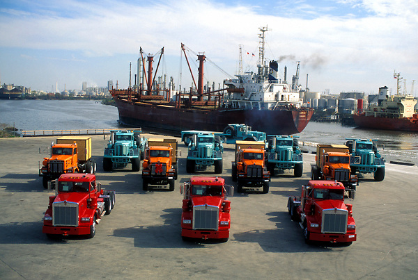 Aerial view of a fleet of parked large transport vehicles with a large ship passing by