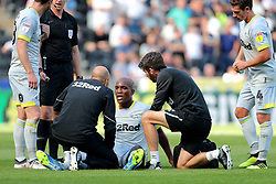 Derby County's Andre Wisdom (centre) receives treatment