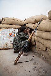 © Licensed to London News Pictures. 28/09/2014. Rabia, Iraq. A female sniper belonging to the Syrian-Kurdish YPJ observes after a colleague shot at a possible Islamic State sniper changing position in the Iraqi border town of Rabia.<br /> <br /> Facing each other across the Iraq-Syria border, the towns of Al-Yarubiyah, Syria, and Rabia, Iraq, were taken by Islamic State insurgents in August 2014. Since then The town of Al-Yarubiyah and parts of Rabia have been re-taken by fighters from the Syrian Kurdish YPG. At present the situation in the towns is static, but with large exchanges of sniper and heavy machine gun fire as well as mortars and rocket propelled grenades, recently occasional close quarter fighting has taken place as either side tests the defences of the other. Photo credit: Matt Cetti-Roberts/LNP