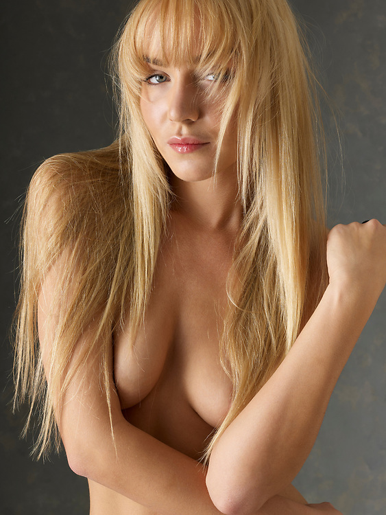 Blond haired topless woman looking seductively at the camera