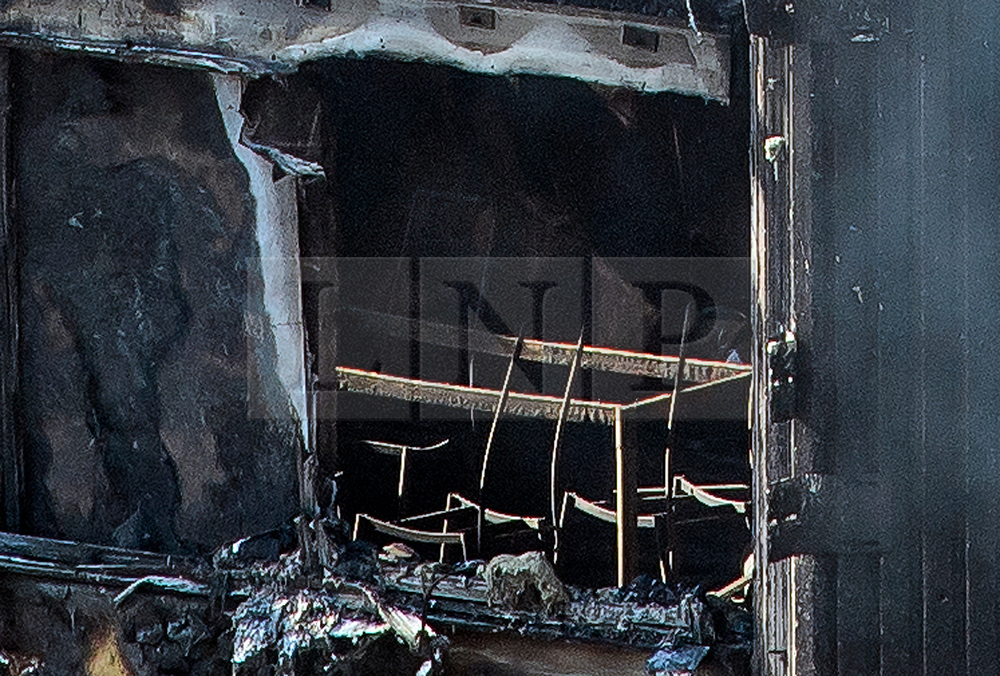 © Licensed to London News Pictures. 15/06/2017. London, UK. What appears to be a table and chairs. The burnt out remains of the inside of some of the apartments can be seen the Grenfell tower block in west London. The blaze engulfed the 27-storey building with hundreds of firefighters attending the scene. Photo credit: Ben Cawthra/LNP