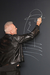 "© Licensed to London News Pictures. 8 April 2014. London, England. Pictured: Jean Paul Gaultier draws a head on the wall and signs it during a photocall. French fashion designer Jean Paul Gaultier opens his exhibition ""The Fashion World of Jean Paul Gaultier - From the Sidewalk to the Catwalk"" at the Barbican Art Gallery, London. The exhibition runs from 9 April to 25 August 2014 and is organised by the Montreal Museum of Fine Arts in collaboration with Maison Jean Paul Gaultier, Paris.   Photo credit: Bettina Strenske/LNP"