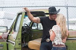 sexy cowboy kissing a blonde girl by an old pick up truck