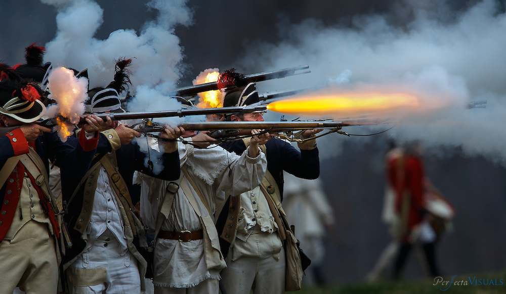 The face of sergeant Kevin Webster of the New Jersey Light Infantry regiment is seen surrounded by the sparking flint and muzzle blasts as Continental troops fire on the British. New Jersey was portraying Delaware light infantry that was in the actual battle.<br /> <br /> Over 300 Revolutionary War reenactors from across the country mustered in Greensboro on March 12 &13 for the Battle of Guilford Courthouse, which originally occurred on March 15, 1781. The reenactment attracts hundreds of participants and thousands of onlookers to see a live recreation of the original battle and life in the combatants camps. American and British troops fire on each other with cannons and flintlock muskets as they advance toward each other on the rolling fields of Country Park in Greensboro, NC, the county seat of Guilford County. During the American Revolutionary War a 2,100-man British force under the command of Lieutenant General Charles Cornwallis defeated Major General Nathanael Greene's 4,500 Americans. The British Army, however, lost a considerable number of men during the battle with estimates as high as 27%. Such heavy British casualties resulted in a strategic victory for the Americans.<br /> <br /> JERRY WOLFORD / Perfecta Visuals