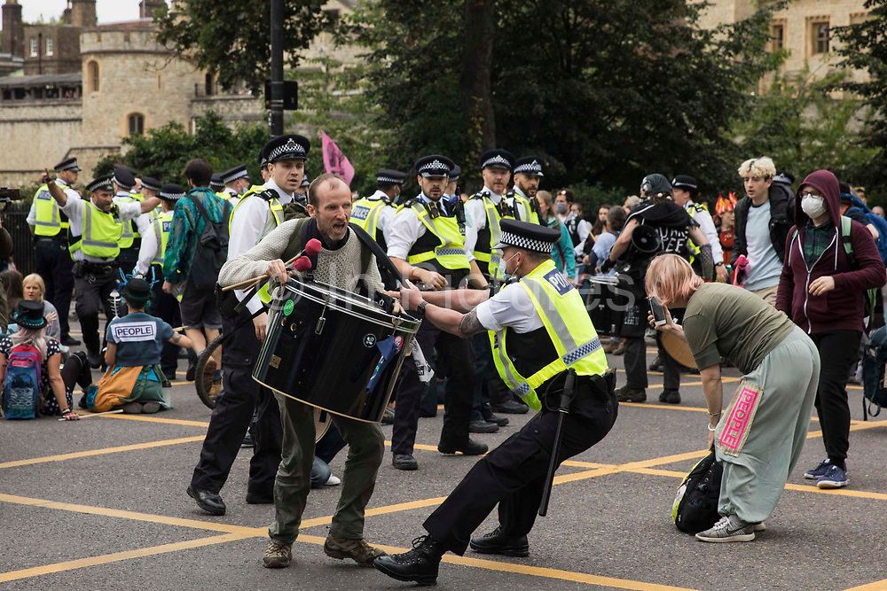 Metropolitan Police officers try to prevent environmental activists from Extinction Rebellion from sitting in the road on the Tower Gateway one-way system during an Impossible Tea Party event on 30th August 2021 in London, United Kingdom. Extinction Rebellion were drawing attention to financial institutions funding fossil fuel projects whilst calling on the UK government to cease all new fossil fuel investment with immediate effect on the eighth day of their Impossible Rebellion protests in London.