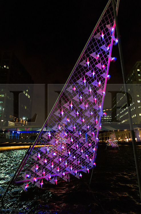© Licensed to London News Pictures. 21/12/2013. London, UK. A wind powered light display called 'fLUMENS' illuminates the Middle Dock at Canary Wharf in London on a windy night. 'fLUMENS' was created by Dutch artist Rombout Frieling and Luuk van Laake who is a former wind engineer now working for DigiLuce and aims to visualise the wind. The 'fLUMENS' are solely powered by the wind and have been built to withstand gusts up to gale force 10 on the Beaufort scale.. Photo credit : Vickie Flores/LNP