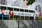 A London bus with advertising for vape brand Blu passes the head of a model as part of a giant ad for SEAT on the side of the IMAX cinema at Waterloo, SE1, on 19th August 2019, in London, England.