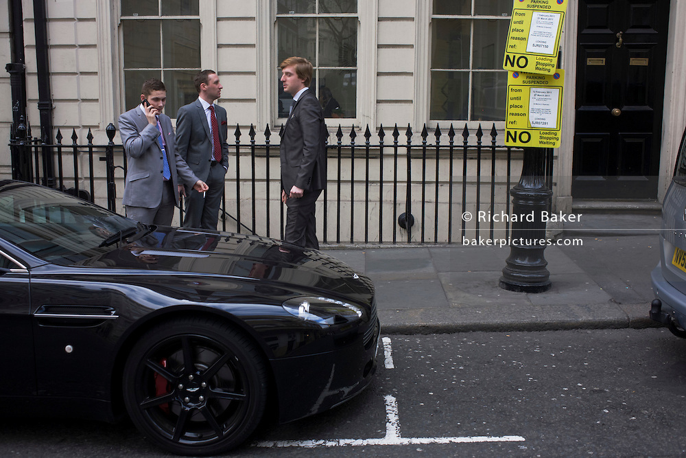 Three wealthy-looking young men in a London street with an unknown black sports car.