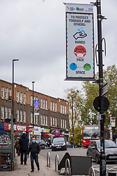 © Licensed to London News Pictures. 17/10/2020. LONDON, UK. One of many social distancing signs in Ealing, west London.  The Office for National Statistics (ONS) has reported that the confirmed coronavirus cases in the capital exceed 67,000, with Ealing having the highest Covid-19 rate amongst London Boroughs at 144 cases per 100.  Following the UK Government's announcement, the capital has today moved from Tier 1 to Tier 2, meaning a ban on indoor social mixing between households in the capital.  Photo credit: Stephen Chung/LNP