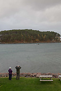A couple looking out to Loch Shieldaig and Shieldaig Island on the 4th November 2018 in Shieldaig, Scotland in the United Kingdom. Shieldaig is a village in Wester Ross in the Northwest Highlands of Scotland.