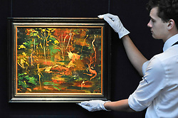 """© Licensed to London News Pictures. 17/11/2017. London, UK.  London, UK.  17 November 2017. A technician hangs """"The Goldfish Pool at Chartwell"""", circa 1962, by Sir Winston Churchill (Est. GBP 50-80k), the final work Churchill ever painted.  Preview upcoming auctions of Modern & Post War British Art and Scottish Art taking place at Sotheby's, New Bond Street, on 21 and 22 November. Photo credit: Stephen Chung/LNP"""