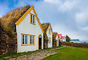 """A farmhouse is said to have stood on the hill at Glaumbær since the Age of the Settlements (900 AD). The present buildings vary in age; the most recent addition having been built in 1876-79, while the oldest – the kitchen, """"long pantry,"""" and middle baðstofa – are believed to have been preserved much as they were in the mid-18th century. The passages connecting the individual units have also remained unchanged for many centuries.<br /> <br /> The form of the farmhouse as it is today is similar to that of many large farmhouses in Skagafjördur from the 18th and 19th centuries. Between 1879 and 1939, the farmhouse at Glaumbær remained unchanged; it was repaired and declared a conserved site in 1947, the year the last inhabitants moved out. An English benefactor, Sir Mark Watson, contributed a gift of £ 200 for the renovation of the farmhouse, which was crucial to its preservation. <br /> <br /> The farmhouse is built of turf, stones, and timber. The walls are built of stones and of pieces of turf layed up in a herringbone pattern, with long turf strips between the layers. The Glaumbær estate provided little rock suitable for building purposes, but it has plenty of good turf, so the walls of the farmhouse contain relatively little rock; it was used only at the base of the walls to prevent damp from rising up into them. Imported timber and driftwood were used in the interior frame and paneling. <br /> <br /> The farmhouse consists of a total of 13 buildings (houses), each of which had its own function. The main unit is the baðstofa, a communal eating/sleeping room, where people sat to do their handiwork. Food was stored and prepared in the pantry and kitchen. The front hall, passages, and south entrance (Brandahús) provided access throughout the farmhouse. One house provided accommodation for the elders and other members of the household. There are two guest rooms, two storerooms, and a smithy (blacksmith's workshop). Many of the pastors of Glaumbær were skilled in metalw"""