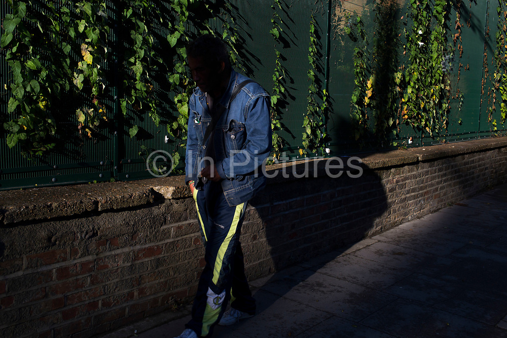 Man walking through a shadow in evening light past a green fence covered in ivy plants growing through it. Whitechapel, East London, UK.
