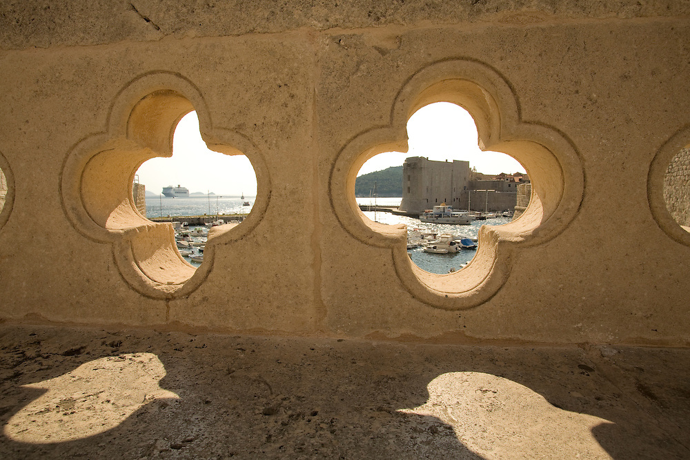 Europe, Croatia, Dalmatia, Dubrovnik.  Fort of St. John and marina, viewed through carved opening in stone wall. The historic center of Dubrovnik is a UNESCO World Heritage site.