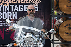 Two sets of wide handle bars! Checking out the Brian Klock designed Jack Daniels limited edition bike at the Indian Foot Print located at the Daytona International Speedway during Daytona Bike Week's 75th Anniversary event. FL, USA. Saturday March 12, 2016.  Photography ©2016 Michael Lichter.