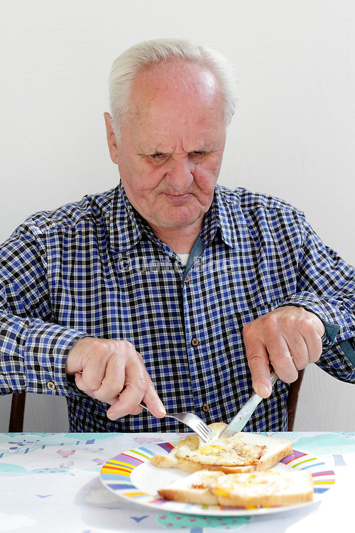 senior male person eating baked egg with bread