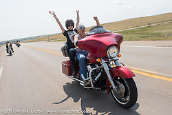 Missi Shoemaker with Shannon Kerr riding north on highway 79 on the Run to the Line for lunch and biker vs Cowboy rodeo games at the Spur Creek Ranch in Newell during the annual Sturgis Black Hills Motorcycle Rally. SD, USA. Wednesday August 9, 2017. Photography ©2017 Michael Lichter.