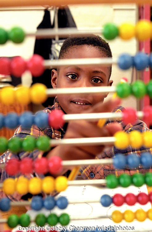 Young primary school child learning maths by counting with an abacus