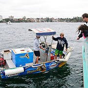 Youn entrepeneurs in a small dinghy selling icecreams to spectator craft at the start of the 2009 Rolex Sydney to Harbour Yacht Race in Sydney Harbour