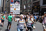 """New York, NY - 30 June 2019. The New York City Heritage of Pride March filled Fifth Avenue for hours with participants from the LGBTQ community and it's supporters. Two women with a sign that reads """"Nancy & Gail 36 years in love, still marching for justice."""""""