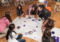 """LHS Seniors (starting lower left) Annie Dionne, Erin Cashman, Lily Chanthasak, Adasha Santos, Rose Therrien, Isabel Gorse and Payal Patel work on posters Thursday afternoon for their """"Purple"""" New Hampshire Humane Society float for the """"Colors For A Cause"""" themed Homecoming parade.  (Karen Bobotas/for the Laconia Daily Sun)"""