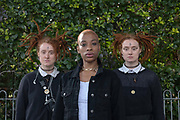 A portrait of a black woman with short hair and two white woman with red dreadlocks pictured in front of a green hedge on the 5th September 2019 in East London in the United Kingdom.
