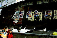 A couple strolls past the Regal Cinema covered with tattered posters of Yasin Malik, the Kashmiri Independence leader.