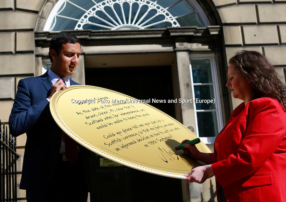 Scottish Labour Deputy Leader Anas Sarwar holding the gigant coin while Leader Worker Alison Dowling signing the coin. <br /> Scottish Labour deputy leader Anas Sarwar and credit union leader worker Alison Dowling deliver a giant pound coin to Bute House. The First Minister's official residence, to highlight uncertainty over what currency an independent Scotland would use.<br /> <br /> Pako Mera/Universal News And Sport (Europe) 07/08/2014