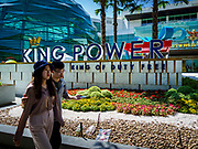 30 OCTOBER 2018 - BANGKOK, THAILAND: Tourists walk past the front of the King Power shopping complex in Bangkok. Vichai Srivaddhanaprabha, owner of King Power, the Thai duty free airport shops, and Leicester City soccer club, died Saturday, 27 October, in a helicopter crash after a soccer match in the UK.  PHOTO BY JACK KURTZ