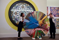 "© Licensed to London News Pictures. 14/09/2018. LONDON, UK. Technicians inspect ""beautiful all round, big toys for big kids, Frank and Lorna, when we are no longer children we are already dead, painting"", 1998, by Damien Hirst (Est. GBP150,000-200,000) in front of ""Epiphany"", 2005, by Damien Hirst (Est. GBP280,000-350,000) at a preview of the ""Yellow Ball: The Frank and Lorna Dunphy Collection"" sale at Sotheby's in New Bond Street.  Frank Dunphy was Damien Hirst's former business manager and mentor.  Over 200 works will be auctioned by Sotheby's on 20 September 2018.  Photo credit: Stephen Chung/LNP"