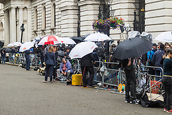 Downing Street, London, July 13th 2016. Occasional light drizzle brings out the umbrellas as world's media gathers outside 10 Downing Street as Prime Minister David Cameron prepares to hand over to Theresa May.