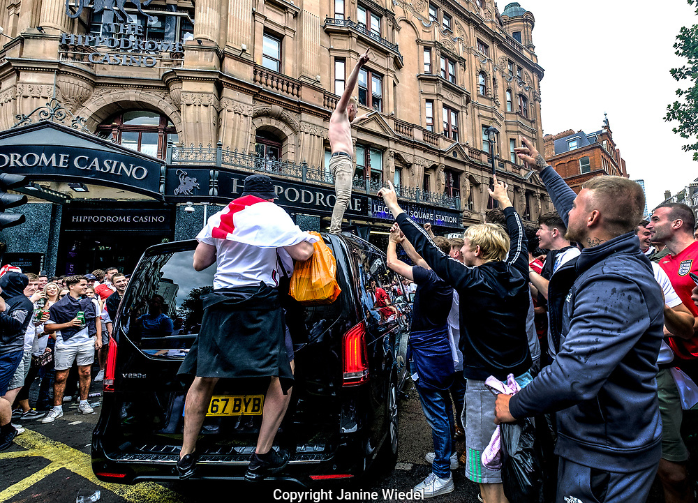 English Football fans jumping on cars in Chring Cross road, Leicester Square in central London before the finals of football match against Italy.  England v Italy Euro 2020 final. 11 July 2021