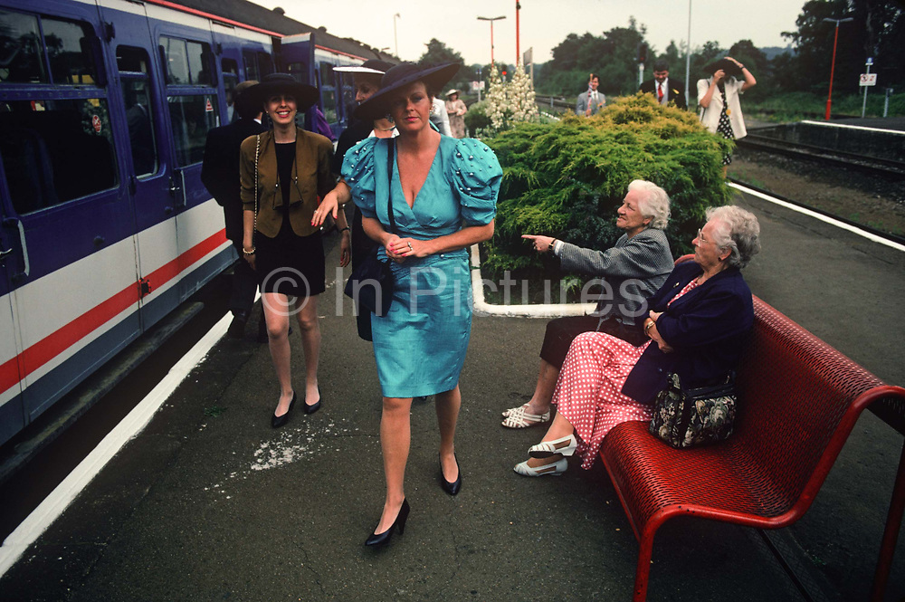 Women watch other ladies arriving from London to attend Royal Ascot Ladies Day, the annual event on the English sporting and social calendar in June, on 18th June 1992, in Ascot, England.