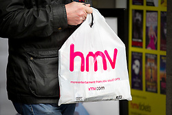 © Licensed to London News Pictures. 15/01/2013. London, UK. A shopper carries an HMV branded bag out of the company's Oxford Street store in London today (15/01/13) after the retailer went in to administration. Photo credit: Matt Cetti-Roberts/LNP