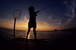 Stock photo of the silhouette of a person fishing from the edge of a pier at sunset