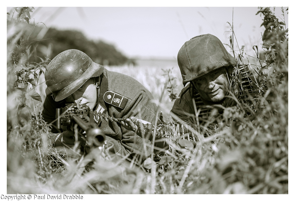 Reenactors portraying a machine gun team from the Panzer Grenadier Division Großdeutschland with an MG42 in its light machine gun role camouflaged in the tree line between two fields. Both soldiers are wearing the iconic German 'coal scuttle' M42 Steel helmet (Stahlhelm) the one on the right is covered with a Splinter pattern (Splittertarnmuster) camouflage helmet cover