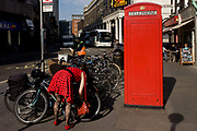 A lady wearing a red dress with black polka dots locks her bike near a red public telephone kiosk. Bending over to attach the lock that might prevent a bike thief - common in the capital and other cities in the UK - she echoes the red of the phone box in Russel Street, the heart of London's theatreland. The red kiosk stands as an iconic piece of architecture that has graced Britain's towns and villages for 70-odd years. These K-series kiosks were largely designed in 1936 by the renowned designer Giles Gilbert Scott. With the increasing use of mobile phones the static phone boxes are still used in remote areas of the UK where mobile service is still patchy and in major towns and cities, their presence is becoming rarer.