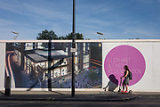 A local scoots past a construction hoarding showing the future regenerated development, on 1st September 2016, at Elephant & Castle, south London, England UK. The regeneration of Elephant is a controversial change to this area of south London where a poor segment of society and more recently a migrant population has traditionally proliferated. With the construction of a new estate called Elephant Park comes a wealthier but less present occupier, more interested in investment than integration.