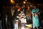 Traditional musicians and storytellers perform among a growing crowd of Moroccans in Djemaa El-Fna square, the heart of the Marrakech medina, Morocco.