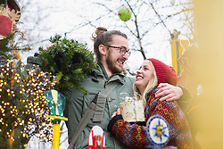 Young man carrying Christmas tree and embracing his girlfriend