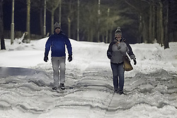 © Licensed to London News Pictures . 24/03/2013 . Burnley , UK . Two pedestrians walk carefully along a snow covered Halifax Road . Snowdrifts are making roads impassable around Burnley overnight (23rd/24th March) as high winds blow snow across roads . Plummeting temperatures and treacherous conditions are reported to have taken the life of a man named locally as Gary Windle . Lancashire Police reported finding a 27 year old man dead in deep snow yesterday (23rd March) afternoon . Photo credit : Joel Goodman/LNP