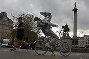 A jogger runs through Trafalgar Square, passing a street artist busker on a painted bike. As the man runs past we see the person busking on the bike, part of his art instillation, sitting on the saddle waiting for tourists to approach him for a picture and donate money. In the background is Nelson's Column, honouring the English naval hero ofr the Napoleonic wars, Admiral Lord Horatio Nelson (1758 – 1805) who stands on top of his 46m (151 ft) high plinth. Trafalgar Square is London's most central landmarks known for its fountains, pigeons and nowadays, its street buskers who entertain the capital's tourism industry.