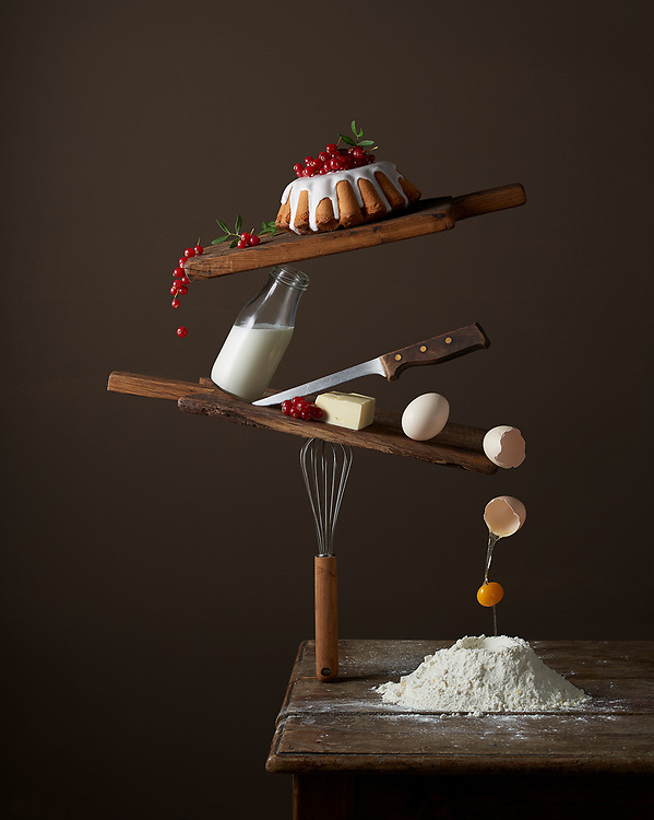Bundt cake ingredients balanced on a rustical table.