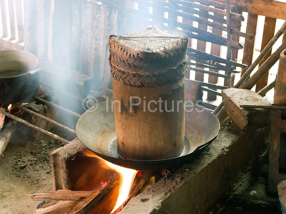 Cooking sticky rice in a bamboo steamer over a wood fire in Ban Chalern, Phongsaly province, Lao PDR. The remote and roadless village of Ban Chalern is situated along Nam Ou river and will be relocated due to the construction of the Nam Ou Cascade Hydropower Project Dam 7.