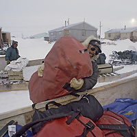 BAFFIN ISLAND, Nunavut, Canada. Inuit Guides load climbing expedition gear into komatik sleds before departing from Clyde River.