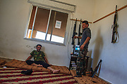Maintaining the security of the  Free Syrian Army HQ stronghold is a responsibility its local armed youth do in shifts.  Members of the FSA are seen coming and going as they hang their AK47 rifles in the wall of the break room on Wednesday, June 27, 2012. (Photo by Vudi Xhymshiti)