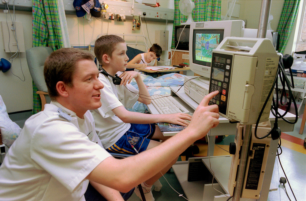 Young boy doing homework on computer in children's ward of London Hospital,
