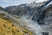 Trampers descend to glacier-carved Dart Valley from Cascade Saddle in Mount Aspiring National Park, Otago region, South Island of New Zealand.